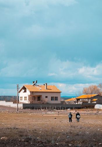 People on field by buildings against sky