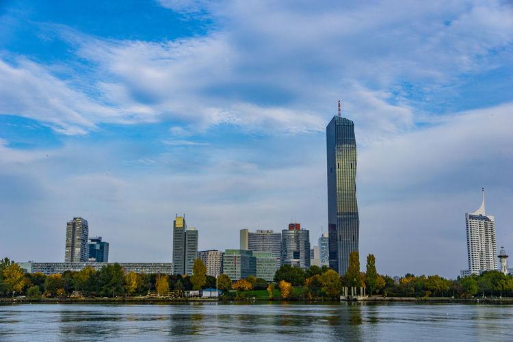 River by modern buildings against sky in city