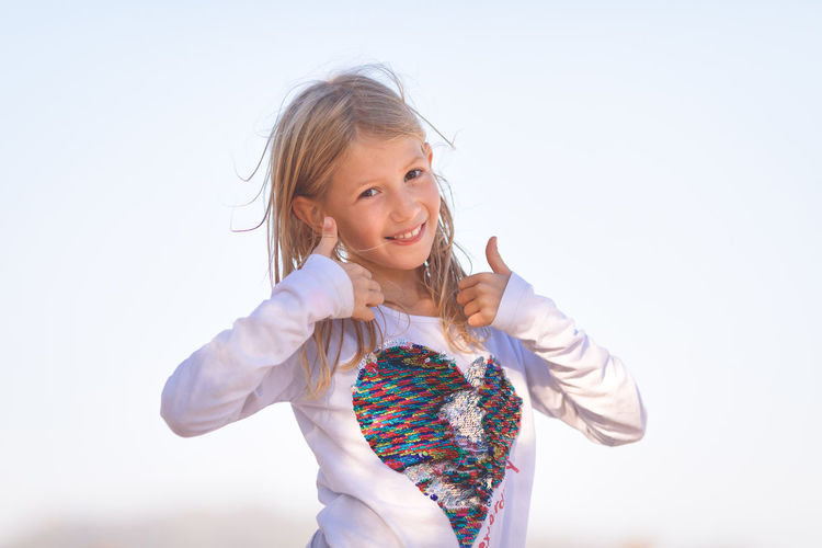 Portrait of smiling girl showing thumbs up signs