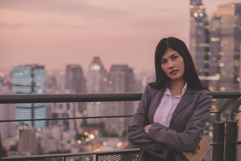 Portrait of confident businesswoman standing by railing at rooftop