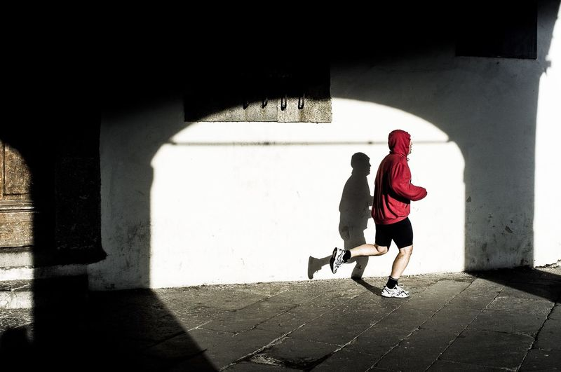Full Length Side View Of Man Jogging Against White Wall