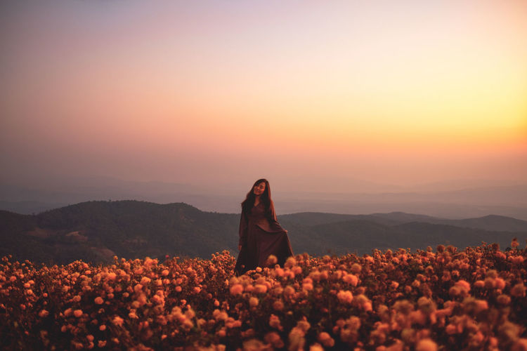 Beautiful woman standing amidst field against sky during sunset