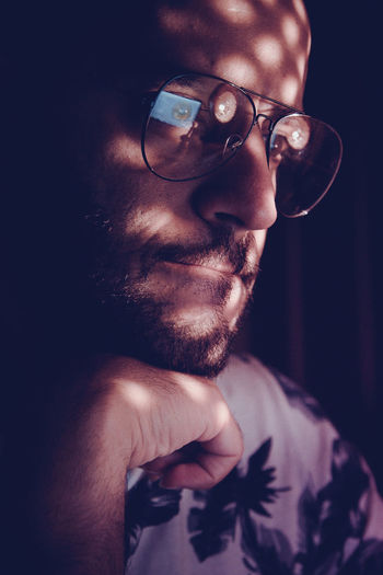 Sunlight falling on thoughtful man wearing eyeglasses in darkroom