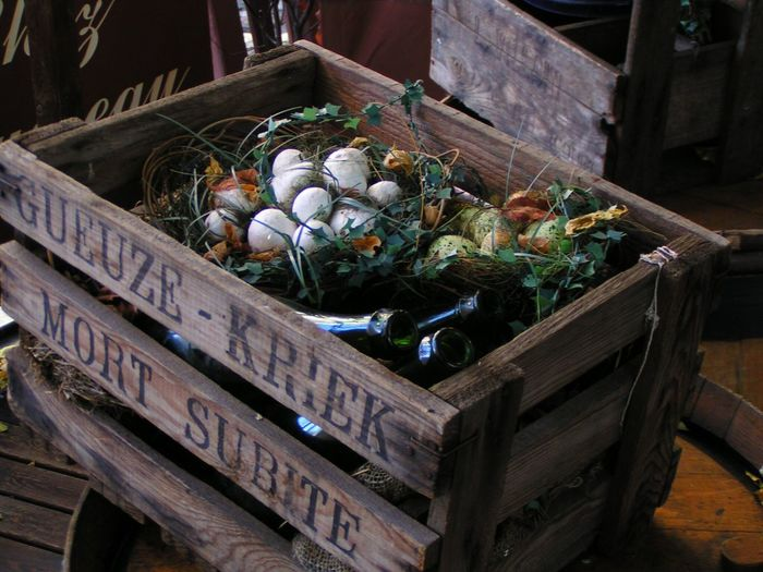 High angle view of eggshells and glass bottles in wooden crate
