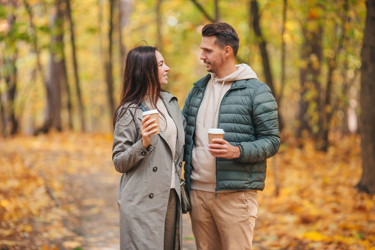 Young couple standing in forest during autumn
