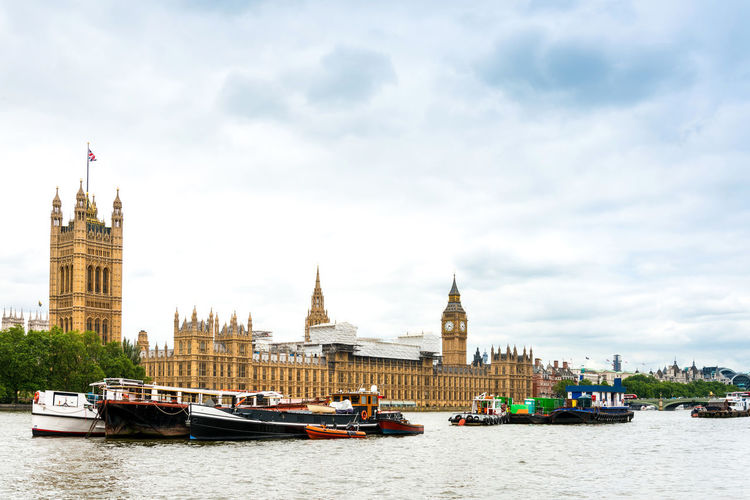 Boats in thames river by houses of parliament and big ben