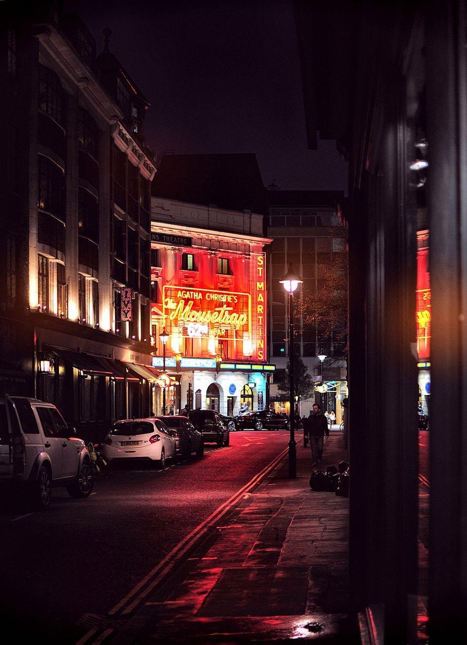 CITY STREET BY ILLUMINATED BUILDINGS AT NIGHT