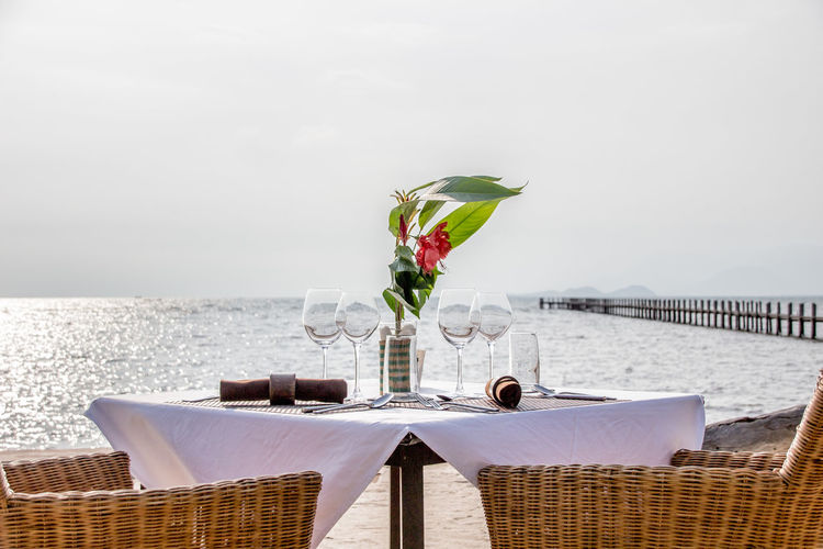 Flower vase and wineglasses on table by sea against sky