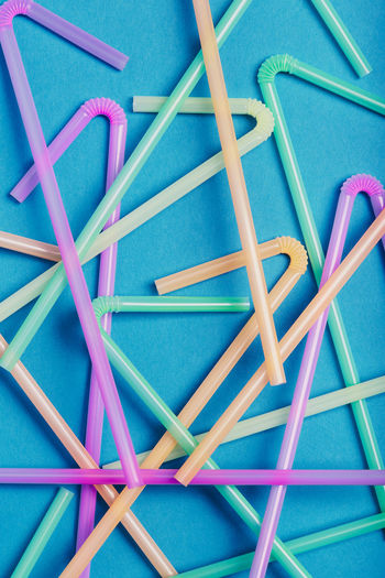 Directly above shot of multi colored drinking straw over blue background