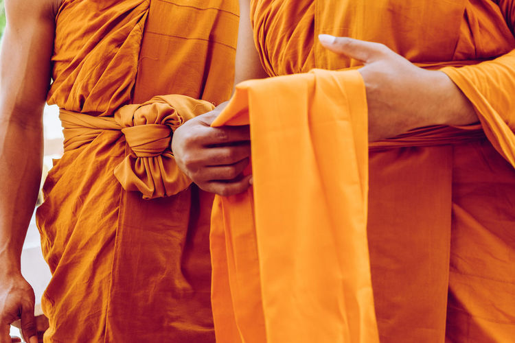 Midsection of monks holding fabric while standing outdoors