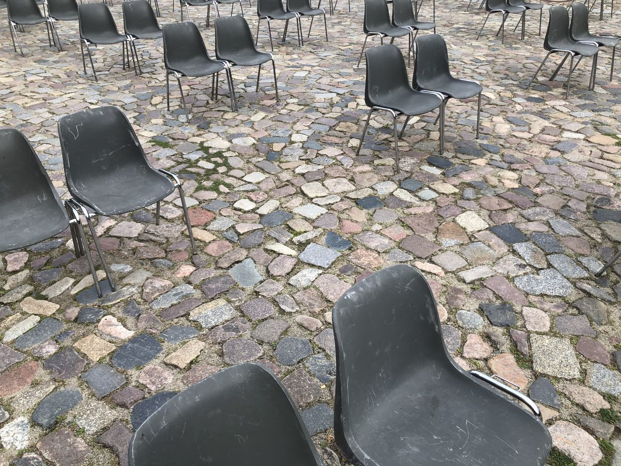 HIGH ANGLE VIEW OF EMPTY CHAIRS ON STREET