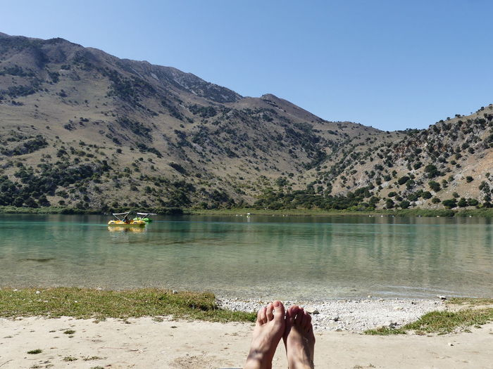 Low section of person relaxing in lake against sky