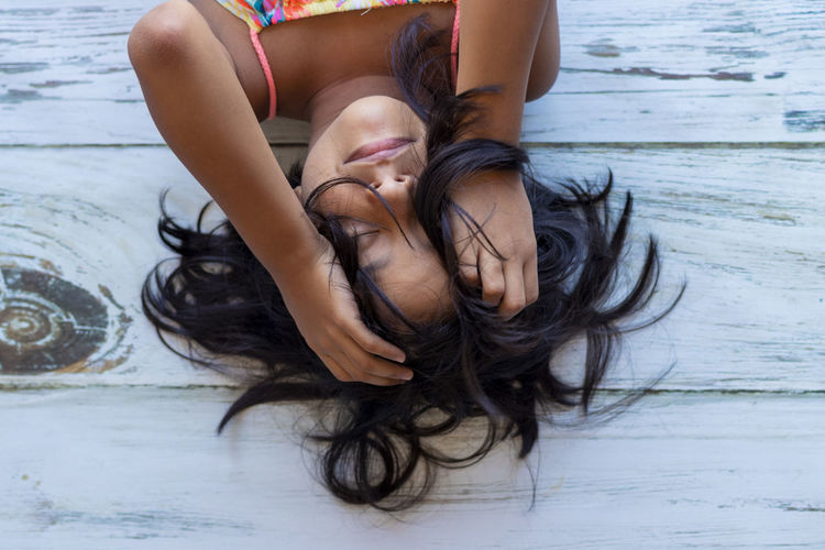High angle view of girl with eyes closed lying on floor