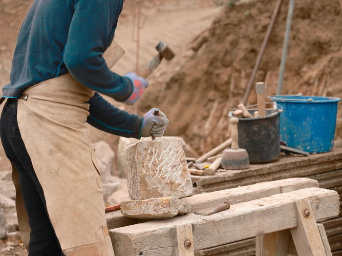 Midsection of craftsperson using hammer and chisel on rock