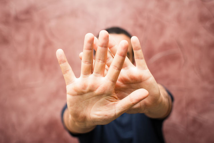 Man gesturing stop while standing against wall