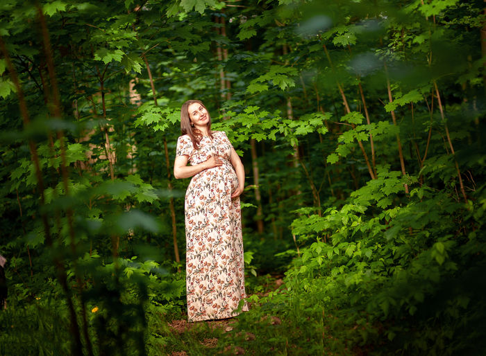 Portrait of pregnant woman touching abdomen while standing in forest