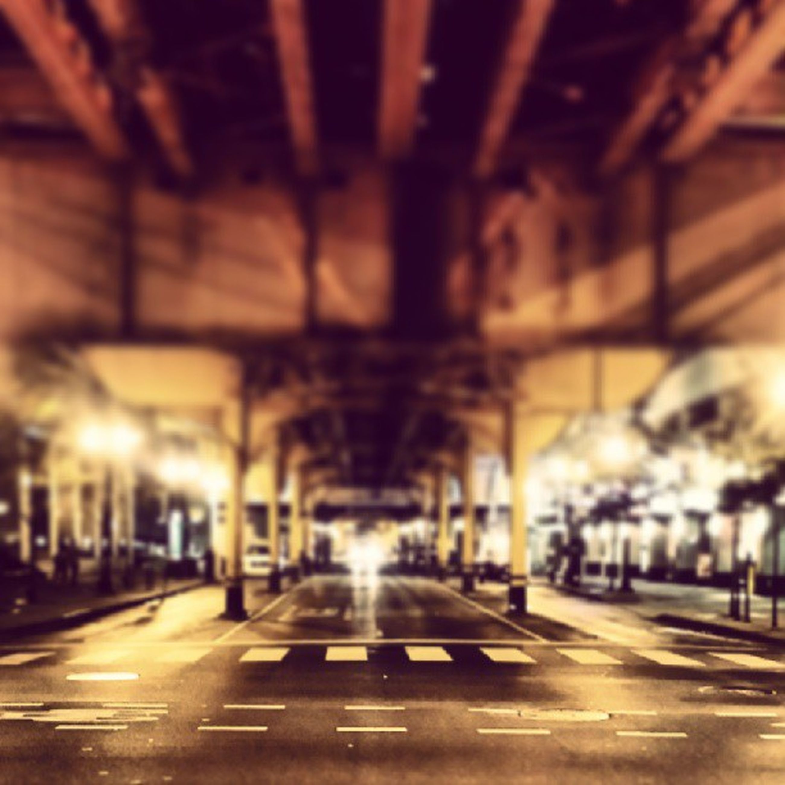 illuminated, architecture, transportation, built structure, city, road, the way forward, street, night, building exterior, lighting equipment, road marking, car, city life, street light, diminishing perspective, city street, empty, land vehicle, incidental people