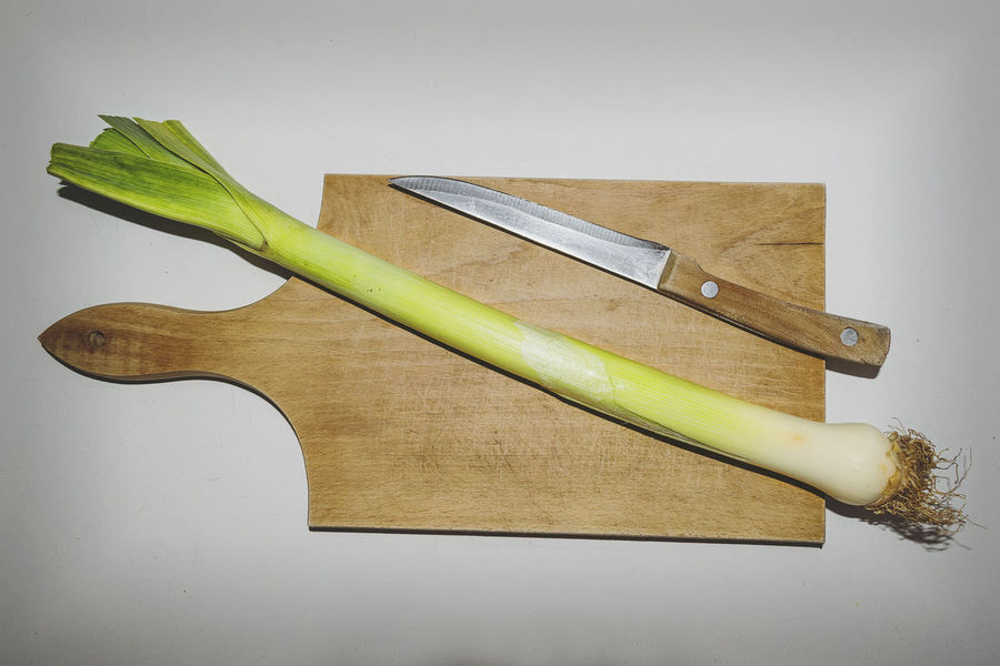 Leek and knife on a wooden cutting board, Table top view Allium Ampeloprasum Leek Natural Close-up Cutting Board Cutting Knife Eating Out Food Food And Drink Foodphotography Freshness Healthy Eating Healthy Food Prep Healthy Lifestyle Healthyfood High Angle View Indoors  Kitchen Board kitchen utensils No People Studio Shot Tabletopphotography White Background Wood - Material Wooden Cutting Board