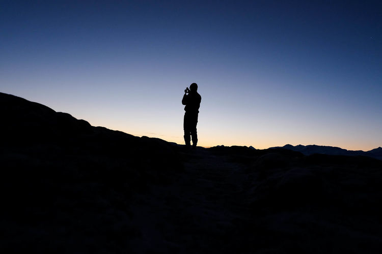 Silhouette man standing on hill against clear sky at dusk