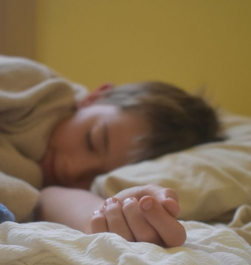 Close-up of boy sleeping on bed at home