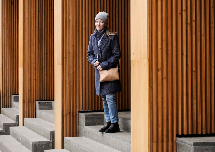 Full length of young woman wearing warm clothing standing on steps