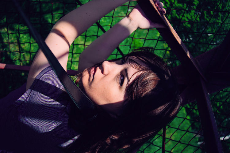 Portrait of young woman against chainlink fence