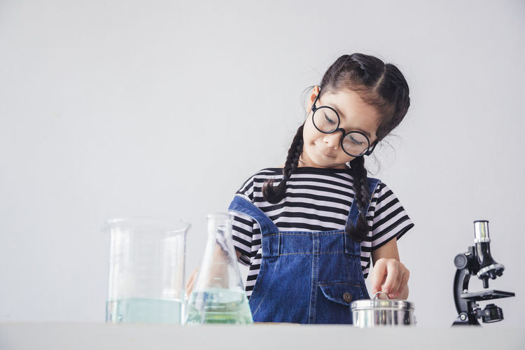 Girl looking away while standing on table