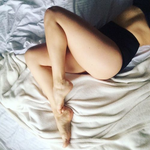 Low section of sensuous woman lying down on bed