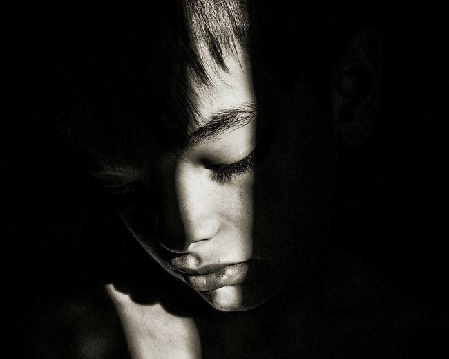 Sunlight Falling On Sad Boy Face In Darkroom