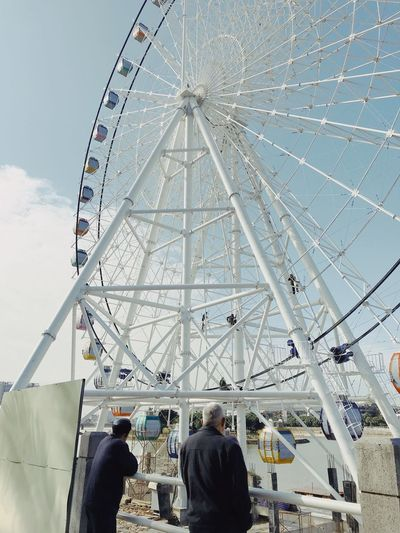 Arts Culture And Entertainment Amusement Park Real People Leisure Activity Ferris Wheel Men Low Angle View Amusement Park Ride Day Women Large Group Of People Outdoors Sky People Adults Only Adult
