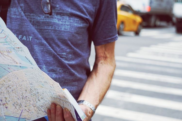 Midsection Of Man Holding Map On Road