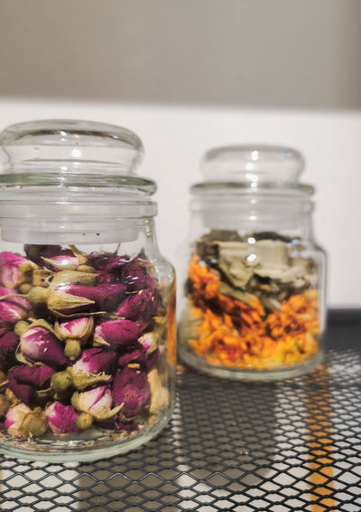 Close-up of flowers in glass jar on table