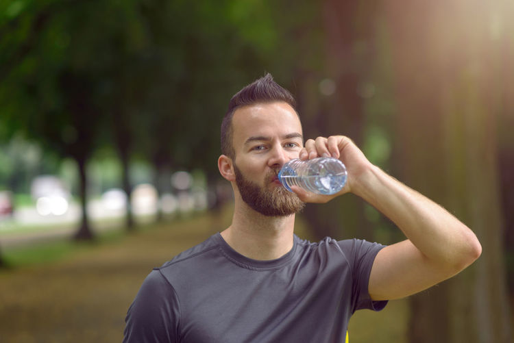 Young man drinking bottled water Athlete Beard Bearded Bottle Concert Drinking Evening Face Fit Fitness Healthy Male Man Morning Outdoors Park Park - Man Made Space Sport Thirsty  Water Young Young Adult