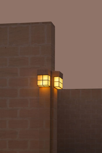 Low angle view of illuminated lamp against wall at night