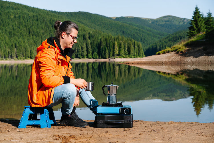 Side view of a man sitting by camping stove by the lake against mountains