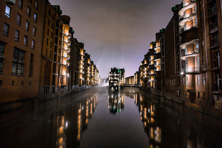 Canal amidst buildings in city at night
