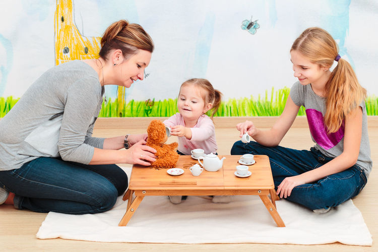 Little girl playing with her mother and elder sister at tea party using child's tea set Cheerful Child Childhood Children Cute Family Fun Girl Home Horizontal Indoors  Joy Kid Mother Parent People Playing Room Set Sister Table Tea Toddler  Toy Woman