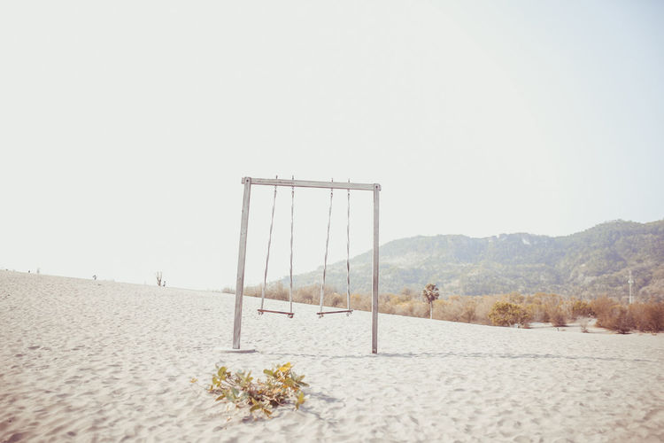 Swing at sand against clear sky