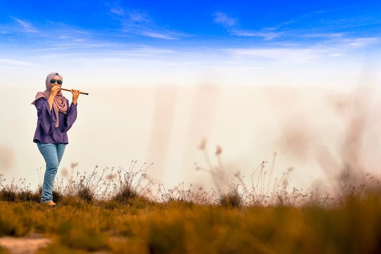Young Woman Playing Flute While Standing On Grassy Field Against Cloudy Sky