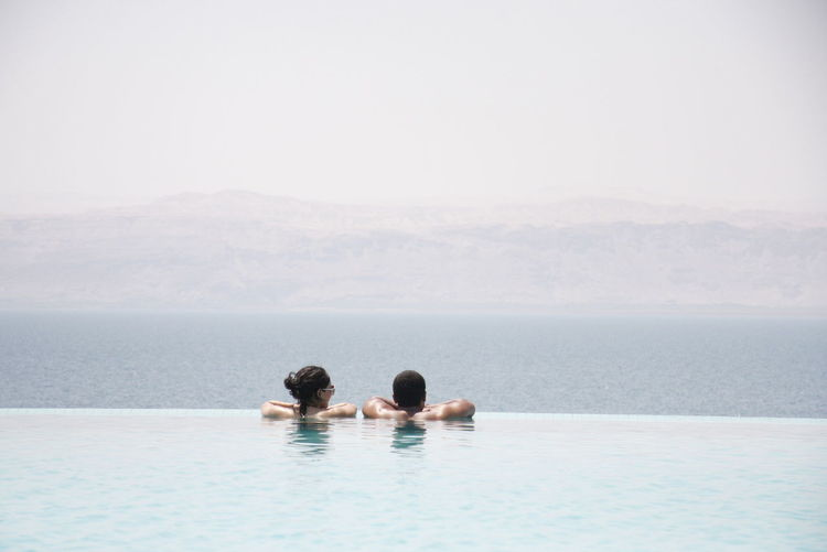 Rear View Of Couple In Infinity Pool Against Sea