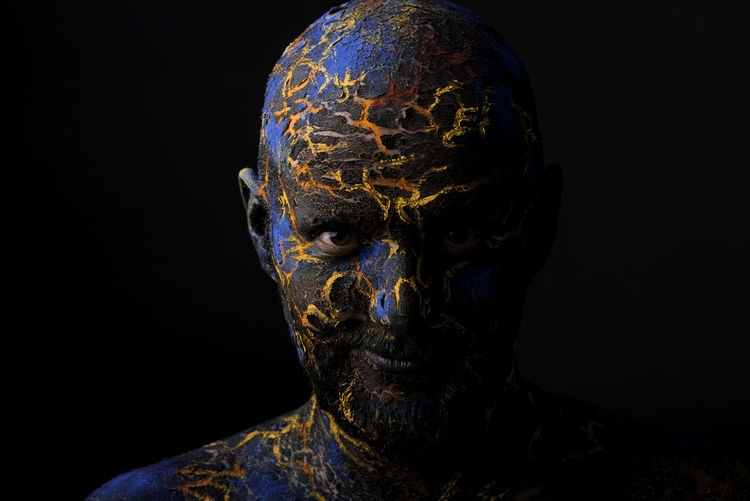 Close-up portrait of mid adult man with body paint standing against black background