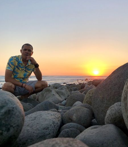 Man crouching on rocks against sea during sunset