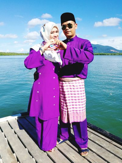 Full length of couple in purple traditional clothing making heart shape with hands by lake on jetty