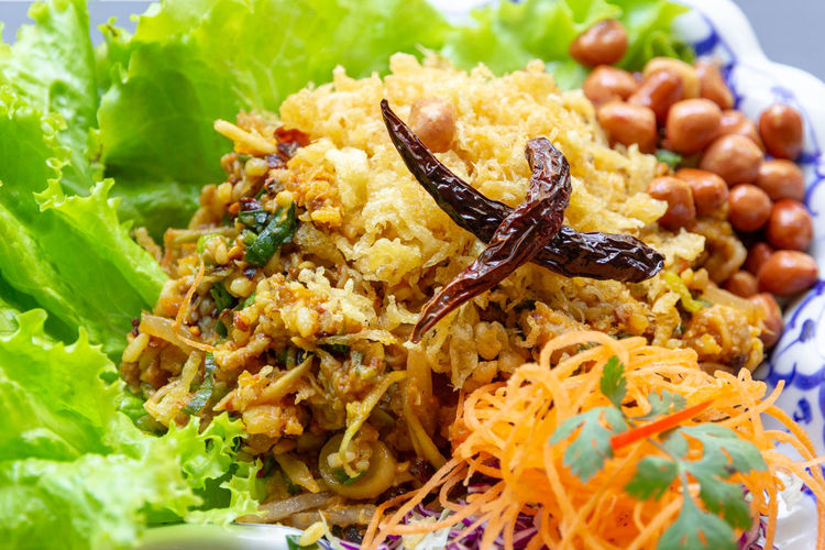 Yam Naem Khao Thot is Spicy Salad of Curried Rice Croquettes, Fermented Pork, Ginger and Peanuts on plate.Thai food Food Food And Drink Freshness Ready-to-eat Healthy Eating Close-up Vegetable No People Plate Still Life Wellbeing Indoors  Serving Size Indulgence Focus On Foreground Selective Focus Salad Meal Rice - Food Staple High Angle View Garnish Temptation Dinner Snack