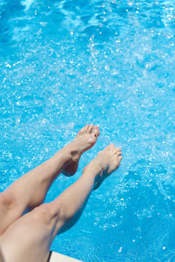 Low Section Of Woman Splashing Water In Swimming Pool