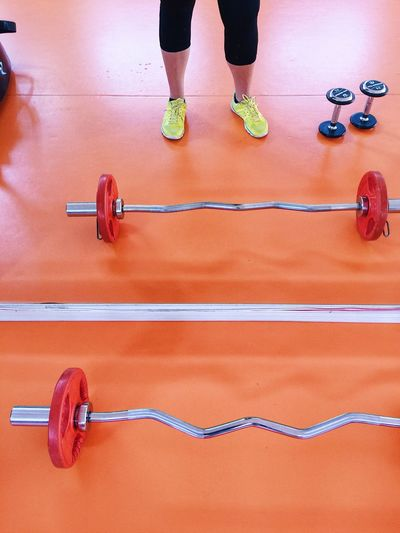 Low Section Of Woman Standing By Barbells And Dumbbell On Orange Floor