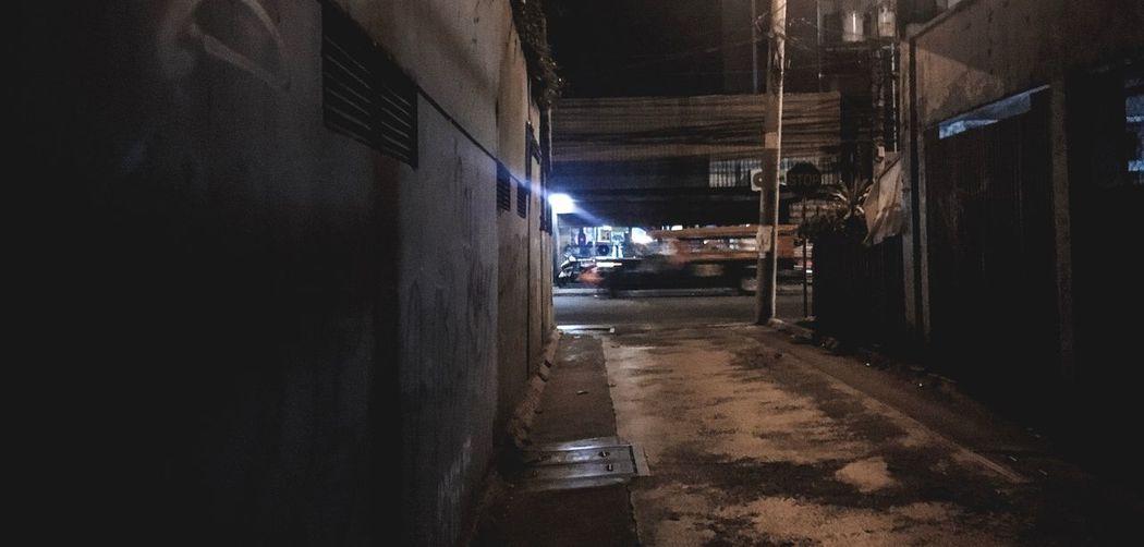 Narrow street amidst buildings at night