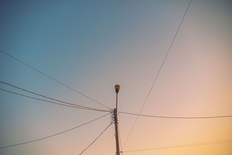 Low angle view of power lines against sky during sunset