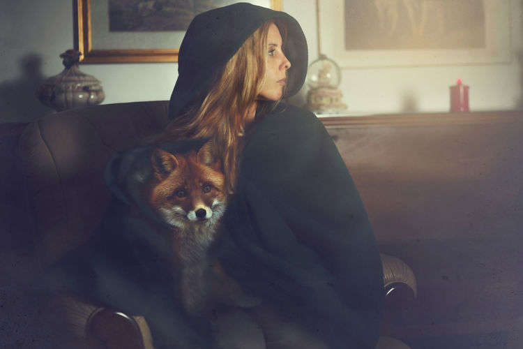 Woman With Fox Covered With Blanket At Home