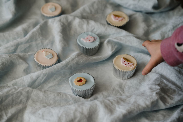 Cropped hand reaching cupcake on fabric
